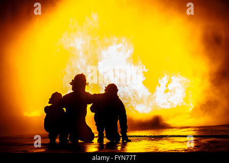 Firefighters in front of a burning tank - Stock Photo
