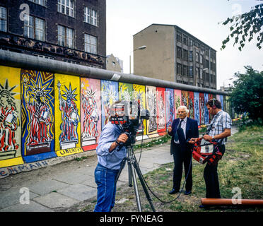 August 1986, CBS TV crew conducting an interview in front of Berlin Wall decorated with Statue of Liberty frescos, - Stock Photo
