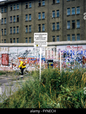 August 1986, Berlin Wall graffitis, warning sign for end of American sector, cyclist, East Berlin building, West - Stock Photo