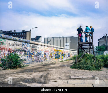 August 1986, Berlin Wall graffitis, people on observation platform looking over the Wall, Zimmerstrasse street, - Stock Photo