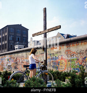 August 1986, young woman with bike, Peter Fechter memorial, graffitis on Berlin Wall, Zimmerstrasse street, Kreuzberg, - Stock Photo