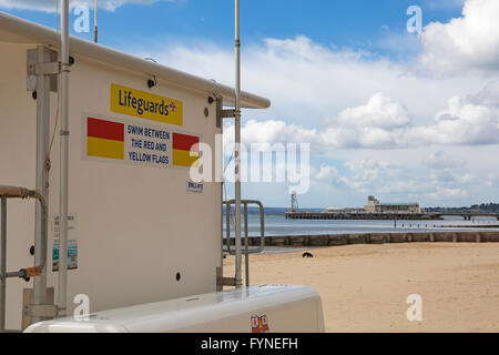 swim between the red and yellow flags sign on RNLI lifeguards kiosk at beach with Bournemouth pier in the distance - Stock Photo