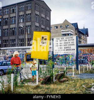 August 1986, woman and boy, leaving American sector warning sign, Berlin Wall graffitis, Zimmerstrasse street, West - Stock Photo