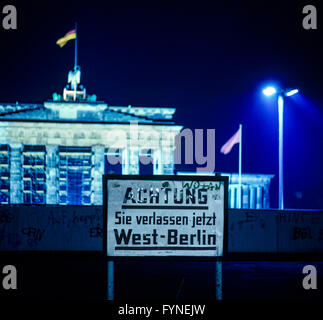 August 1986, leaving West Berlin warning sign front of the Berlin Wall, Brandenburg Gate at night in East Berlin, - Stock Photo