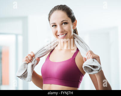 Beautiful sporty woman with towel relaxing at the gym after working out, healthy lifestyle and fitness concept - Stock Photo