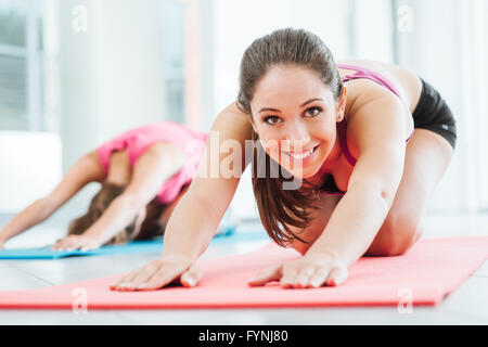 Girls at the gym doing stretching exercises on a mat, one is smiling at camera - Stock Photo