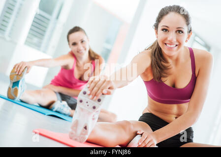 Smiling young women at the gym doing a stretching exercise for legs on a mat, fitness and health concept - Stock Photo