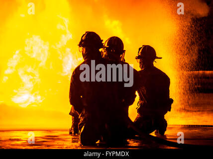 Three firefighters kneeling in front of fire - Stock Photo