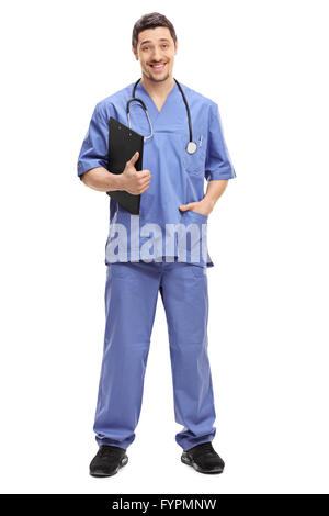 Full length portrait of a young doctor in a blue uniform holding a clipboard and smiling isolated on white background - Stock Photo