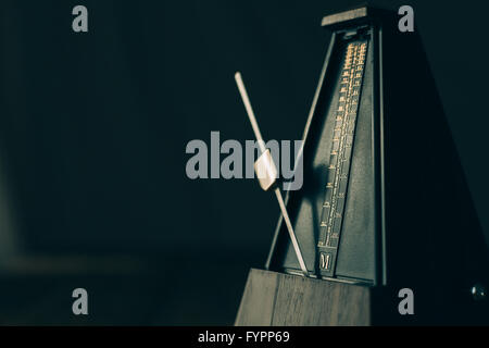 Vintage metronome, on a dark background. - Stock Photo