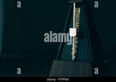 Vintage metronome, on a dark background. - Stock Photo