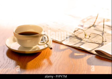 Cup of coffee, with newspaper and glasses, on a bright sunny morning. - Stock Photo