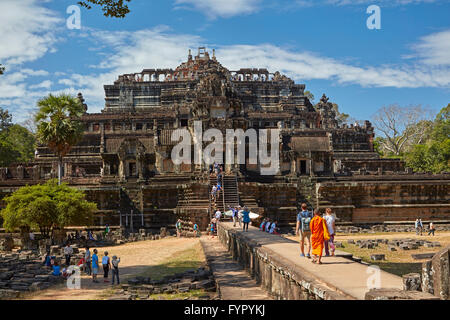 Monk on causeway and Baphuon temple (11th century), Angkor Thom temple complex, Angkor World Heritage Site, Siem - Stock Photo