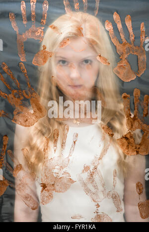Young woman behind plastic sheet covered with handprints