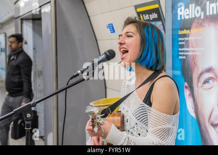 Jazz Mino sings and plays the ukulele as she busks for passengers passing through Waterloo underground station, - Stock Photo