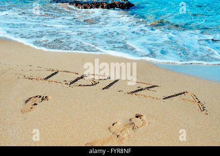the word Ibiza written in the sand of a beach in Ibiza Island, Balearic Islands, Spain - Stock Photo