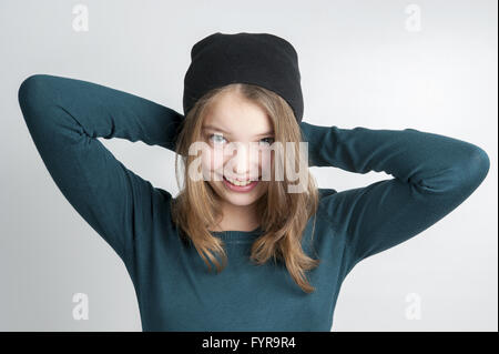Cute little girl holds hands behind head. - Stock Photo