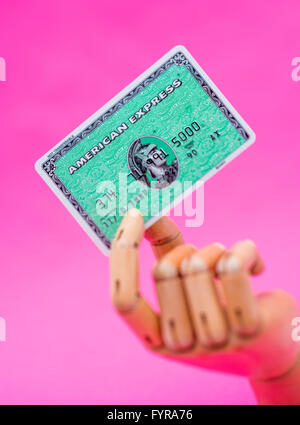 Wooden mannequin hand holding an American Express card - Stock Photo