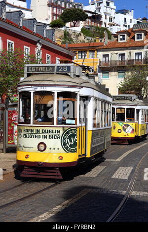 Famous tram 28 in Lisbon carrying tourists round the old town - Stock Photo