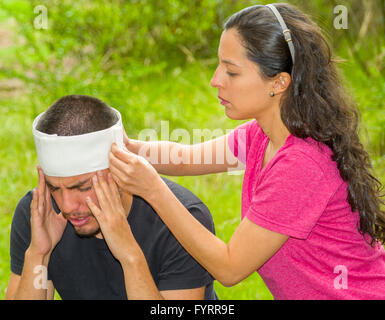 Young man with head injury receiving treatment and bandage around skull from woman, outdoors environment - Stock Photo