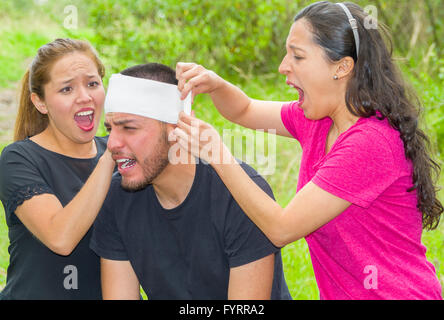 Young man with head injury receiving treatment and bandage around skull from two women, outdoors environment - Stock Photo