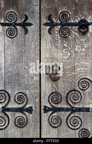 Old oak wooden door and ornate ironwork. Cotswolds, UK - Stock Photo