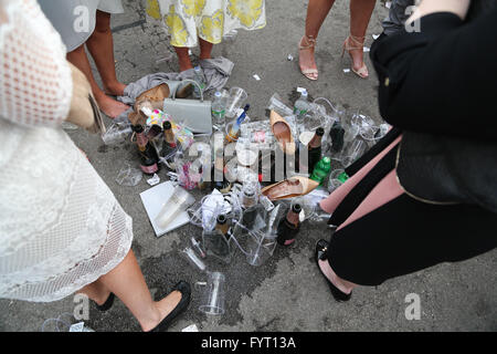 Women surround a pile of empty cups, bottles and shoes at the 2016 Grand National at AIntree Racecourse in Liverpool, - Stock Photo