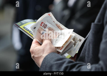 A man holds a wad of cash at the 2016 Grand National at AIntree Racecourse in Liverpool, UK. - Stock Photo