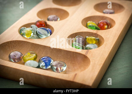 Traditional Mancala boardgame with glass pieces on wooden table - Stock Photo