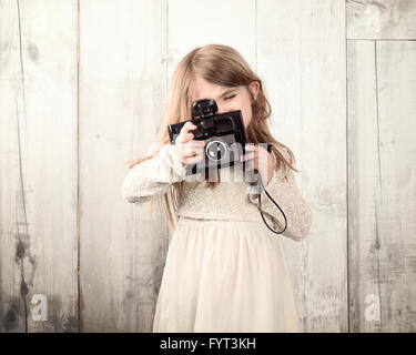 A child photographer is taking a photo with an old film camera against a white wood wall for an art or creativity - Stock Photo