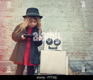 A little hipster child is wearing a hat and holding a tablet with her robot friend downtown for a happiness or technology - Stock Photo