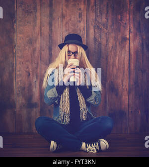 A young hipster woman is drinking a coffee drink against a wood background. She has glasses and a hat on.