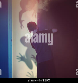 A scared child is looking inside of a closet bedroom at black evil monster ghosts in the background for imagination - Stock Photo