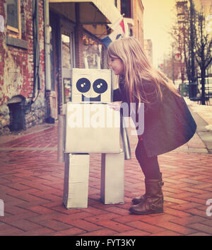 A little girl is hugging a metal cardboard robot downtown against a brick wall outside for a friendship or inventor - Stock Photo