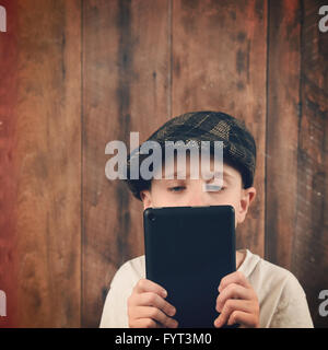 A boy is holding a technology tablet and reading a screen. The child has a vintage hat with a wood bg for communication - Stock Photo