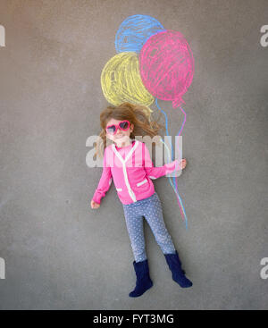 A cute little girl with sunglasses is holding creative chalk balloons drawn on the sidewalk for a imagination, summer - Stock Photo