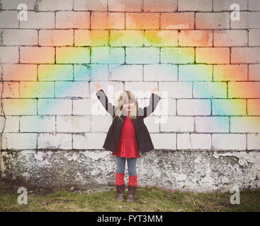 A happy little girl is standing against an old brick wall with a colorful rainbow and her hands are raised for a - Stock Photo