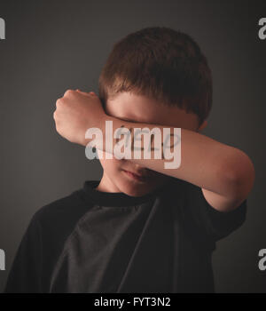 A young child is hiding his eyes with a writing message of help on his arm for a social issue, bully or sadness - Stock Photo
