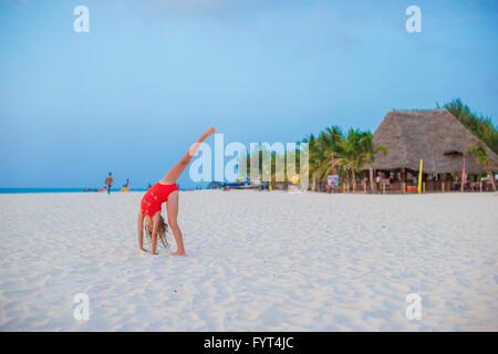 Adorable little girl having fun making cartwheel on tropical beach at sunset - Stock Photo