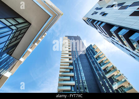 One point perspective looking straight up towards clear blue sky from ground level of tall skyscraper buildings - Stock Photo