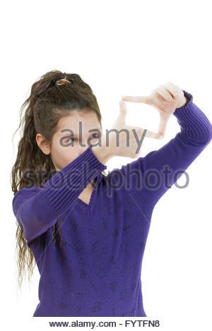 smiling schoolgirl simulates camera photographing - Stock Photo