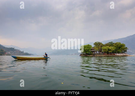 Nepalese man paddling on Phewa Lake in Pokhara, Nepal - Stock Photo