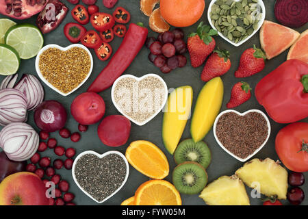 Paleo diet health and super food of fruit, vegetables, nuts and seeds in heart shaped bowls on slate background, - Stock Photo