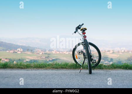 Bicycle standing alone on the road with a view on the valley, mountains and village - Stock Photo