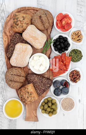 Italian food snacks with bread rolls on an olive wood board with salami, feta cheese, figs, nuts, seeds and oil - Stock Photo