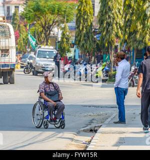 Nepali man in wheelchair on Lakeside in Pokhara, Nepal - Stock Photo