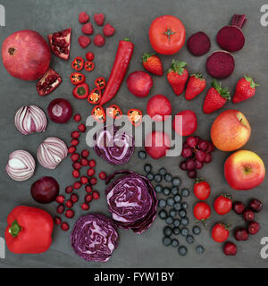 Red and purple health food with a selection of fruit and vegetables,  high in vitamins, anthocyanins and antioxidants. - Stock Photo
