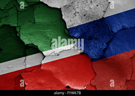 flags of Chechnya and Russia painted on cracked wall - Stock Photo