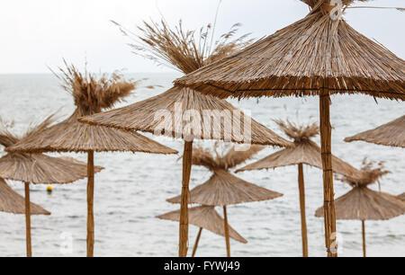 Straw umbrellas on sea background - Stock Photo