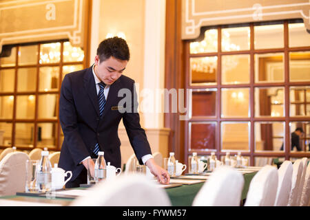 people setting table in luxury dining room - Stock Photo